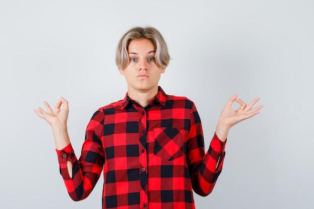 Hübscher teenager, der mudra-geste in kariertem hemd zeigt und verwirrt aussieht. vorderansicht.