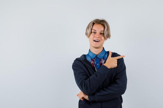 Hübscher teenager, der nach rechts in hemd, hoodie zeigt und froh aussieht, vorderansicht.