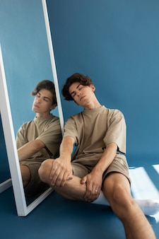 Hübscher teenager, der neben einem spiegel sitzt