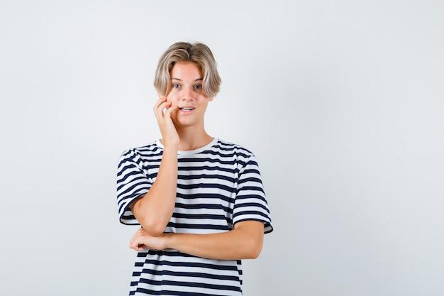 Hübscher teenager, der sich in gestreiftem t-shirt an die wange lehnt und aufgeregt aussieht. vorderansicht.