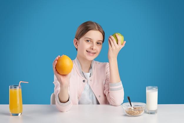 Hübscher teenager, der sie mit einem lächeln ansieht, während sie frisches obst und müsli mit milch essen und orangensaft zum frühstück trinken