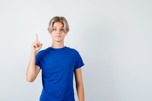 Hübscher teenager im blauen t-shirt, der nach oben zeigt und intelligent aussieht, vorderansicht.