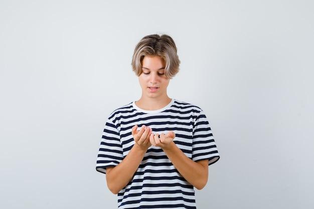 Hübscher teenager im gestreiften t-shirt, der seine handflächen betrachtet und nachdenklich aussieht, vorderansicht.