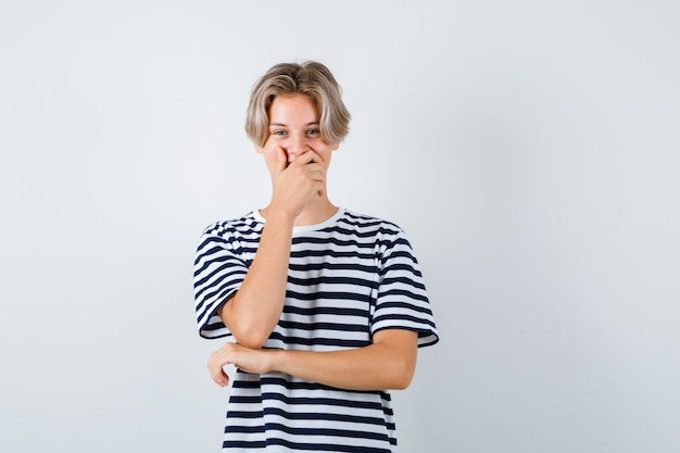 Hübscher teenager im gestreiften t-shirt mit der hand auf dem mund und glücklich aussehend, vorderansicht.