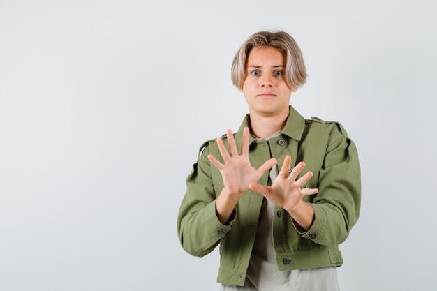 Hübscher teenager in grüner jacke mit kapitulationsgeste und verängstigtem blick