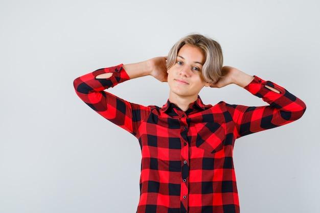 Hübscher teenager mit händen hinter dem kopf in kariertem hemd und entspannt aussehend. vorderansicht.