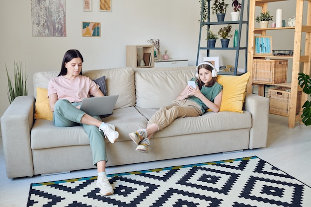 Hübscher teenager mit kopfhörern und ihre ernsthafte mutter in freizeitkleidung mit modernen mobilen geräten beim entspannen auf der weichen couch zu hause