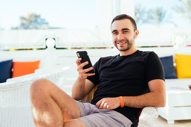 Hübscher tourist liest und schreibt sms auf dem handy während des entspannens im straßencafé.
