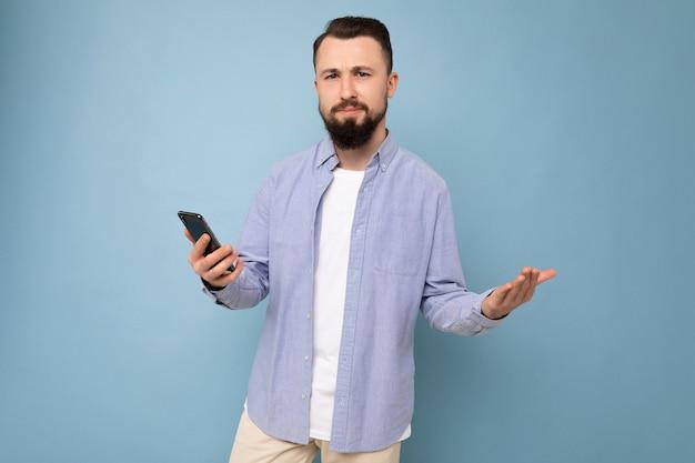 Hübscher trauriger junger brünetter unrasierter mann mit bart, der ein stylisches weißes t-shirt und ein blaues hemd trägt, isoliert auf blauem hintergrund mit leerem raum in der hand und mit telefon-sms-betrachtung