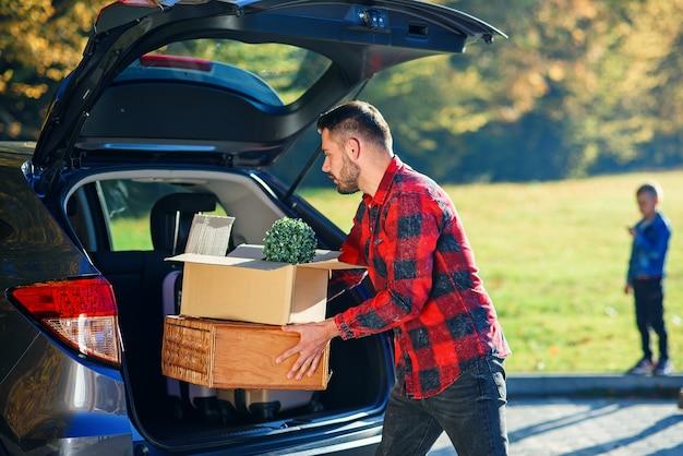 Hübscher trendiger bärtiger mann lädt gepäck in den kofferraum, der auf einer familienurlaubsreise geht.