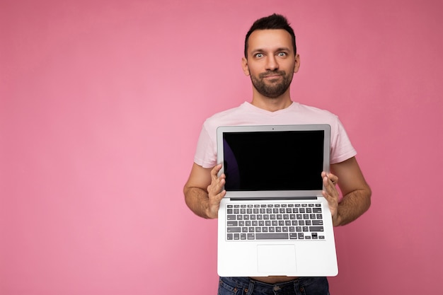 Hübscher überraschter mann, der laptop-computer hält und kamera im t-shirt auf lokalisiertem rosa betrachtet
