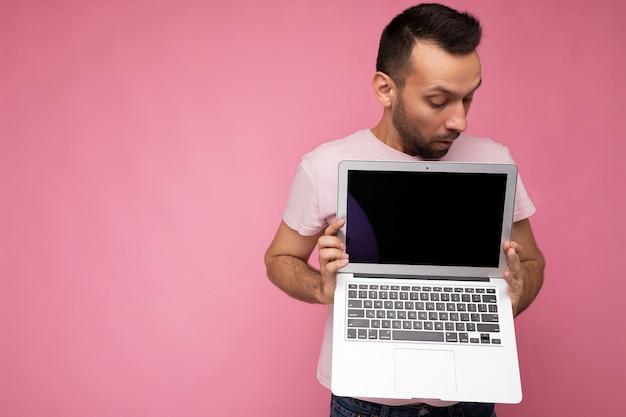 Hübscher überraschter und erstaunter mann, der laptop-computer hält und computermonitor im t-shirt an betrachtet