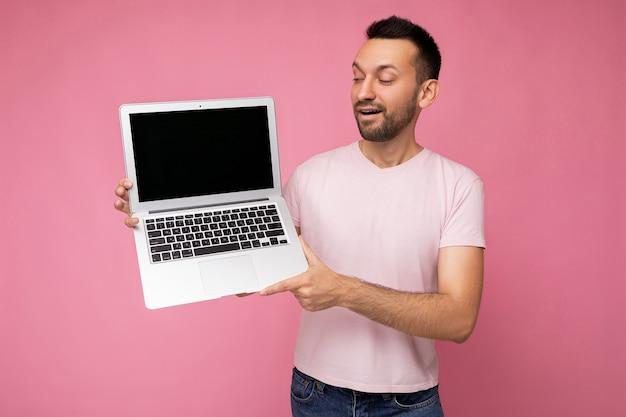 Hübscher überraschter und glücklicher brunet-mann, der laptop-computer hält und netbook-monitor im t-shirt auf lokalisiertem rosa hintergrund betrachtet
