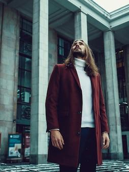 Hübscher überzeugter gut gekleideter mann mit dem bart, der weg draußen schauen aufwirft. modernes reiches männliches modell im roten wintermantel und in der weißen strickjacke