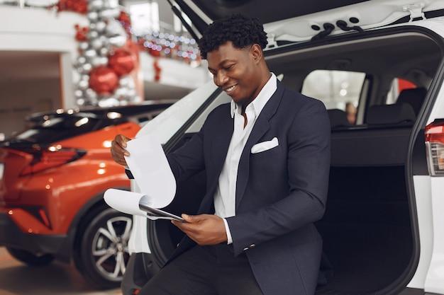 Hübscher und eleganter mann in einem autosalon