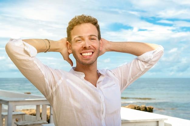 Hübscher und erfolgreicher kaukasischer mann, der sich auf dem strandstudenten am mediterranen ufer entspannt und lächelt
