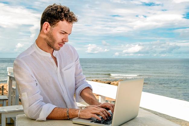 Hübscher und erfolgreicher kaukasischer mann in einem stilvollen gut gekleideten arbeiten mit einem laptop am strand. freiberufliche und fernarbeit. business student am mediterranen ufer