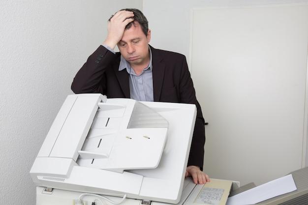 Hübscher und gestresster mann, der ein kopiergerät benutzt