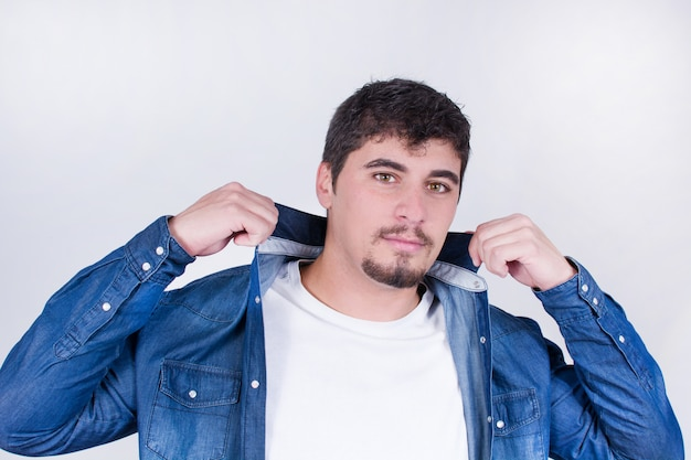 Hübscher und junger mann, der mit dem t-shirt lokalisiert aufwirft