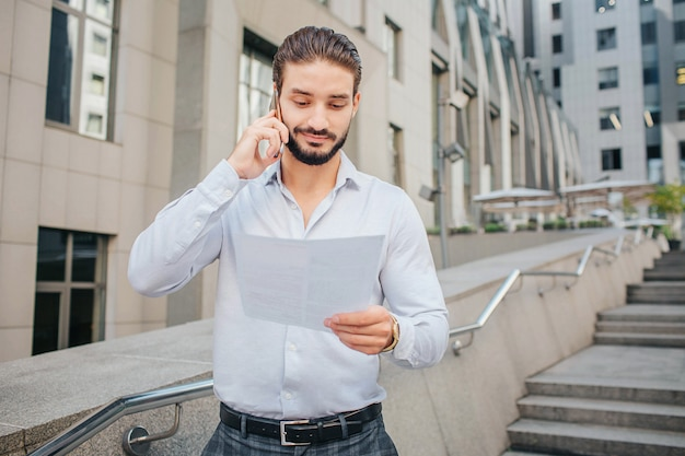 Hübscher und positiver junger mann steht auf stufen. er hält ein stück papier in der hand und lächelt. geschäftsmann spricht am telefon. er sieht sich das dokument an.