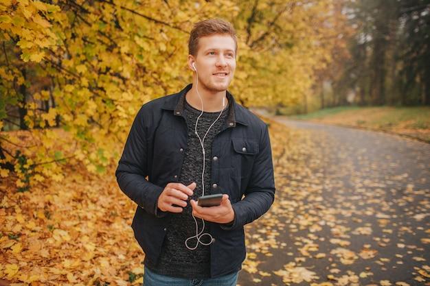 Hübscher und positiver junger mann steht im park und freut sich. er hört musik über kopfhörer.