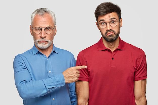 Hübscher unrasierter ernsthafter ernsthafter mann in brille und formellem hemd zeigt seinem ahnungslosen kollegen an, erfahren zu sein, runzelt verwirrt die stirn, trägt ein rotes t-shirt, steht drinnen zusammen