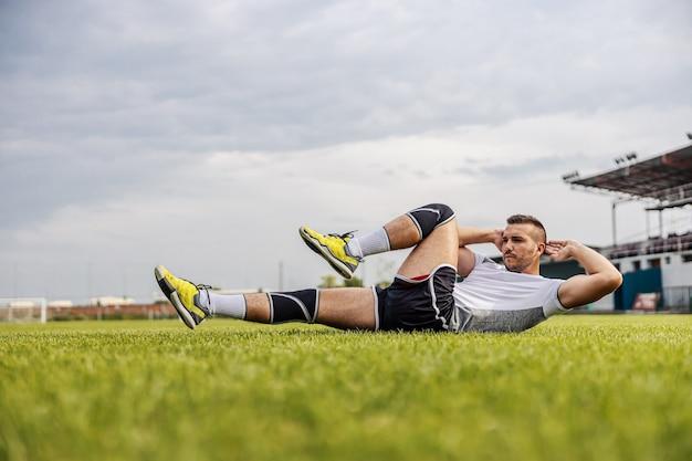 Hübscher unrasierter fußballspieler in form, der sit-ups auf dem feld tut.