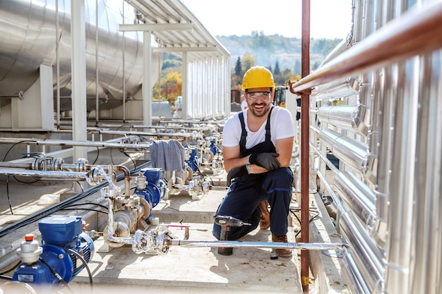 Hübscher unrasierter kaukasischer arbeiter in arbeitskleidung und mit helm auf kopf, der neben öltank kniet und kamera betrachtet.
