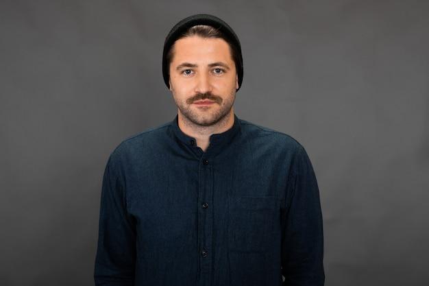 Hübscher unrasierter kerl in gestrickter mütze, die auf grauem studiohintergrund aufwirft