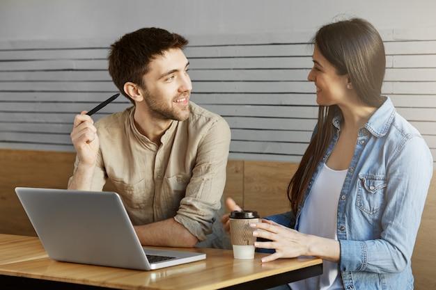 Hübscher unrasierter männlicher freiberufler, der auf einem treffen im café sitzt, dem kunden das projekt zeigt und über arbeitsdetails spricht.