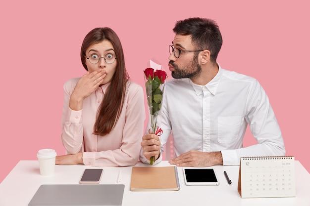 Hübscher unrasierter mann, der freundin küsst, die verwirrten ausdruck hat, schöne rosen gibt, romantische beziehungen hat, perfektionisten ist