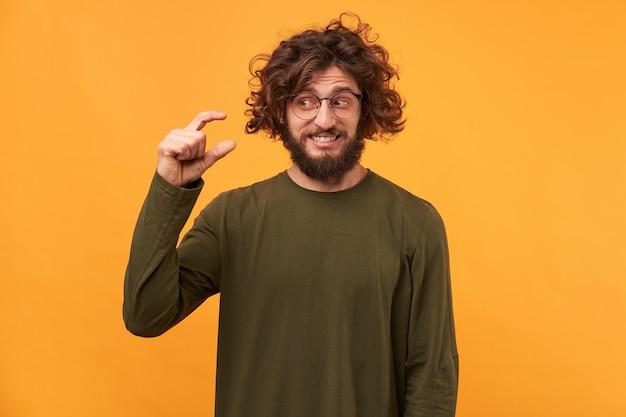 Hübscher unrasierter mann mit dunklem lockigem haar und dicken borsten, zeigt etwas winziges mit den händen