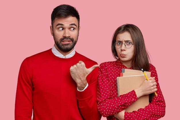 Hübscher unrasierter mann trägt roten pullover, zeigt auf unzufriedene schöne frau, die grimasse macht, orgnaizer und spiralblock trägt