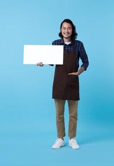 Hübscher unternehmer asiatischer mannangestellter, der leere plakatwand in der hand auf blau zeigt.