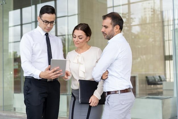 Hübscher unternehmer, der colleag daten über tablet-computer zeigt