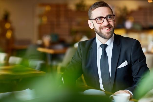 Hübscher unternehmer, der vom café arbeitet
