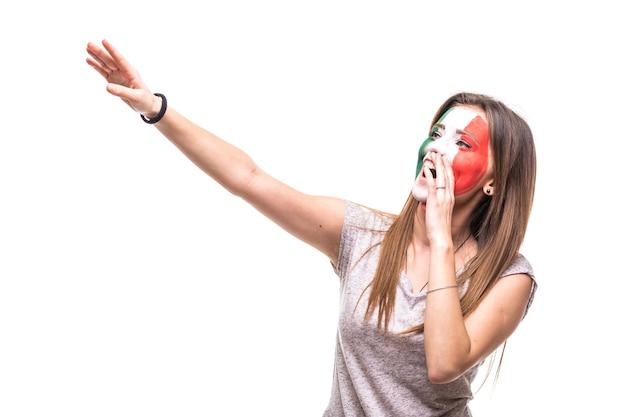 Hübscher unterstützerfan der mexikanischen nationalmannschaft gemaltes flaggengesicht erhalten glücklichen sieg, der spitze hand schreit. fans emotionen.