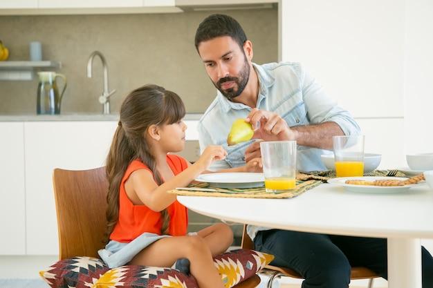 Hübscher vater, der seinem mädchen obst gibt, während sie zusammen in der küche frühstücken