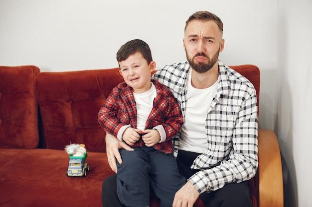 Hübscher vater mit kind auf dem sofa