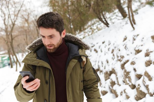 Hübscher verwirrter junger mann, der winterjacke unter verwendung des mobiltelefons beim gehen im freien trägt