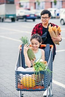Hübscher vietnamesischer mann hält papiertüten mit lebensmitteln, die vor ihm einkaufswagen mit seiner glücklichen schönen freundin drin schieben. lustiger familieneinkauf.