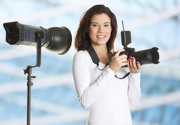 Hübscher weiblicher fotograf, der im studio arbeitet