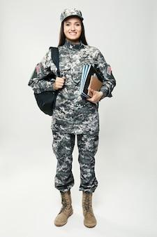 Hübscher weiblicher kadett der militärschule auf grau
