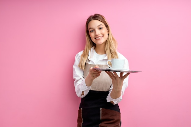 Hübscher weiblicher kellner, der tasse kaffee lokalisiert auf rosa wand anbietet