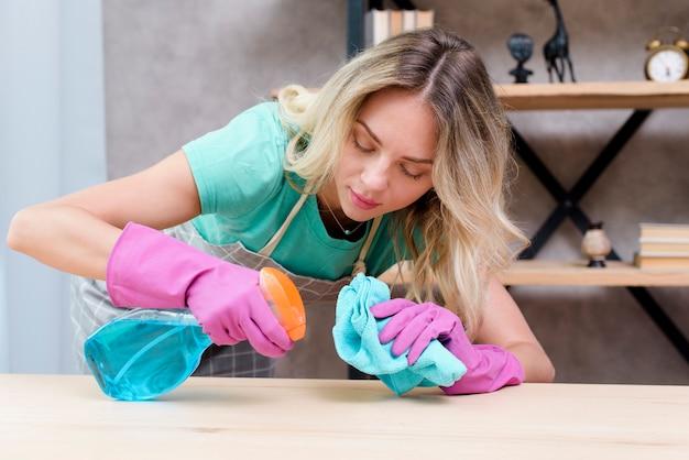 Hübscher weiblicher reiniger, der hölzernen schreibtisch mit reinigungsmittelspray und -stoff säubert