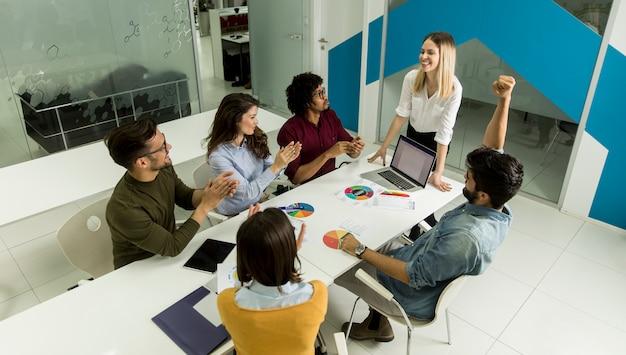 Hübscher weiblicher teamleiter, der mit mischrassegruppe von personen im büro spricht