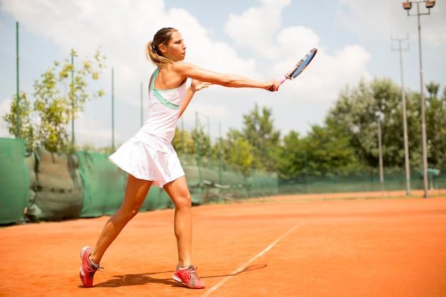Hübscher weiblicher tennisspieler, der auf gericht an einem sonnigen tag spielt