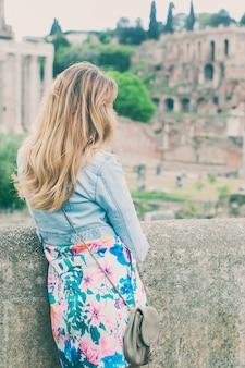 Hübscher weiblicher tourist auf den ruinen des forum romanum in rom, italien