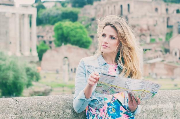 Hübscher weiblicher tourist, der eine karte auf den ruinen des forum romanum in rom, italien sucht