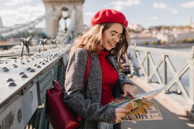 Hübscher weiblicher tourist, der stadtplan mit lächeln betrachtet